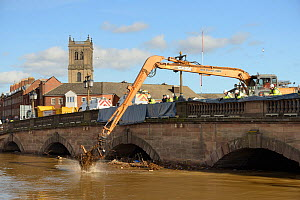 Crane removing debris piling up against the River Severn bridge in Worcester after a period of heavy rain, Gloucestershire, February 2014. - Nick Upton