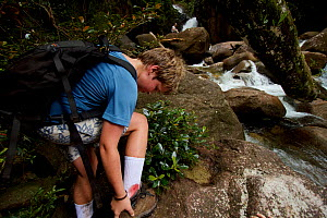 Russell Laman removing his boot to check the leach bite which is bleeding, Gunung Palung National Park, Borneo. August 2010 Model released. - Tim  Laman