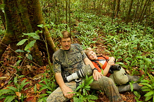 Photographer Tim Laman with son Russell taking a rest in tropical rainforest, Gunung Palung National Park, Borneo. August 2010 Model released. - Tim  Laman