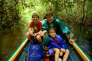 Orangutan researcher Cheryl Knott and children ride boat down river from Cabang Panti Research Station, Gunung Palung National Park, Borneo. August 2010 Model released.  -  Tim  Laman
