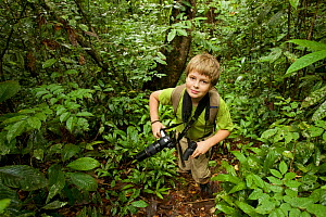 Young boy Russell Laman hiking in the rain forest, Gunung Palung National Park, Borneo. August 2010 Model released.  -  Tim  Laman