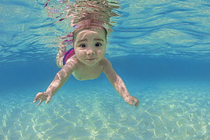 RF - Baby age five months, swimming underwater in the ocean.  Caribbean Sea, Cayman Islands, British West Indies. Model released. - Alex Mustard