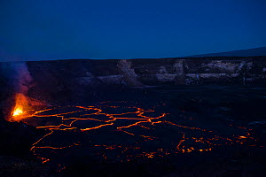 Hot lava fountains at a subduction zone at the edge of a lava lake, covered by plates of partially solidified cooled lava floating on its surface, in a pit within Halemaumau Crater, Kilauea Volcano, H... - Doug Perrine