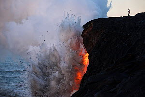 An unauthorized hiker in a restricted zone venturing out onto an unstable sea cliff over a lava tube where hot lava from the 61G flow from Kilauea Volcano enters the ocean from the open end of a lava...  -  Doug Perrine