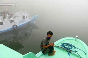Man wearing an anti-pollution mask on a boat on the River Kumai, Tanjung Puting National Park, Central Kalimantan, Borneo, Indonesia, October 2015. In the time of illegal fires, the air becomes unbrea... - Enrique Lopez-Tapia
