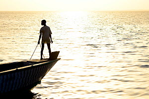 Person silhouetted on bow of boat at sunset, fishing village of Cacheu, Guinea Bissau, February 2015.  -  Enrique Lopez-Tapia