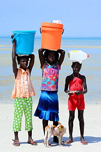Portrait of three girls, with containers on head  to collect water, and dog, Orango Island, Bijagos UNESCO Biosphere Reserve, Guinea Bissau, February 2015.  -  Enrique Lopez-Tapia