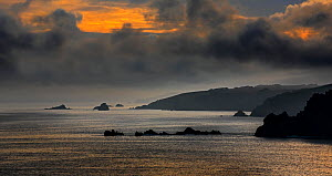 Silhouette of cliffs at the Pointe de Penharn at sunrise with storm clouds, Cléden-Cap-Sizun, Finistère, Brittany, France, September 2015. - Philippe Clement