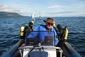 Three people in dive boat, with divers getting ready to go in water, Lamlash Bay, Isle of Arran, South Arran Marine Protected Area, Scotland, UK, August 2016. - SCOTLAND: The Big Picture