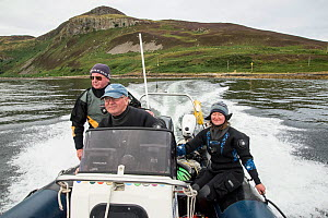 Three people including driver and two divers in dive boat with Holy Island in the background, Lamlash Bay, Isle of Arran, South Arran Marine Protected Area, Scotland, UK, August 2016.  -  SCOTLAND: The Big Picture