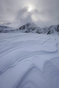 Wind created patterns in layers of packed snow on Meall Dearg with Am Bodach in background, Aonach Eagach, Glencoe, Scotland, UK, February 2017.  -  SCOTLAND: The Big Picture