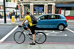 Commuter cyclist in advanced stop lane alongside illegally positioned car, Angel, London Borough of Islington, England, UK, July 2015.  -  Pat  Tuson