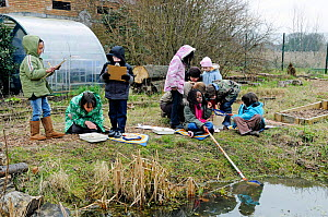Group of children with their teacher pond dipping in winter, Stoke Newington East Reservoir, now Woodberry Wetlands, London Borough of Hackney, England, UK, March 2010.  -  Pat  Tuson