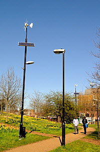 Wind and solar powered lamppost or lamp post alongside conventional lamppost with people passing, Mile End Park, London Borough of Tower Hamlets, England, UK, March 2014.  -  Pat  Tuson