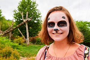 Teenage girl visiting the panda enclosure at the zoo, with panda facepaint. Beauval Zoo, France.  August 2017. Model released.  Please contact us to order / licence these images.  -  Eric Baccega