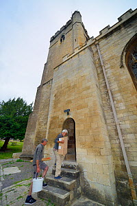 Nest box for Common swifts (Apus apus) carried by Roger Becket and Peter Grayshon into Holy Trinity church to be fitted in the bell tower, Bradford-on-Avon, Wiltshire, UK, June.  -  Nick Upton
