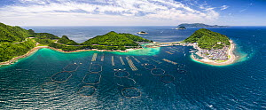 Aerial view of the small island of Kashiwa-jima, with pens in the foreground for aquaculture. The large pens hold tuna.  Kochi Prefecture, Japan - Tony Wu
