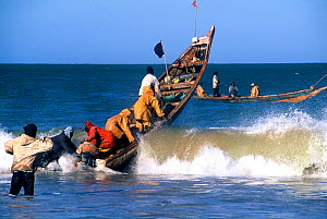 Fishermen launching boat into sea at the edge of the Banc d'Arguin National Park UNESCO World Heritage Site, Mauritania. - Enrique Lopez-Tapia