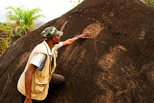 Man with petroglyphs, neolithic rock art. Lopé National Park, Ecosystem and Relict Cultural Landscape of Lopé-Okanda UNESCO World Heritage Site, Gabon. - Enrique Lopez-Tapia