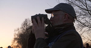 Birdwatcher waiting to see a murmuration of Common starlings (Sturnus vulgaris), Ham Wall RSPB Reserve, Somerset Levels,  England, UK, December.  -  John Waters