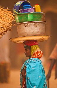 Ouled Rachid tribeswoman carying bowls and buckets on her head, Kashkasha village near Zakouma National Park, Chad, 2010. - Jabruson