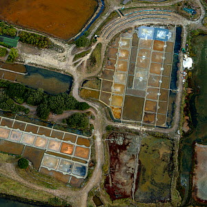 Looking down at salt evaporation ponds and salt piles surrounded by the Salt Marshes of Olonne, Vendee, France, July 2017. The colours are produced by the concentration of algae or halobacteria that l... - Loic Poidevin