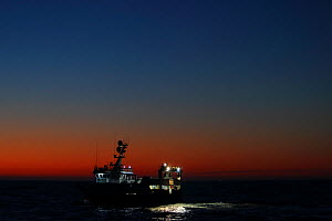 Dawn breaking with fishing vessel 'Harvester' shooting her fishing gear. North Sea. March 2016.  Property released.  -  Philip  Stephen