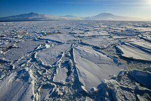 Sea ice, with Mount Terror (left) and Mount Erebus,  Ross Island, Ross Sea, Antarctica. Photographed for The Freshwater Project  -  Michel  Roggo