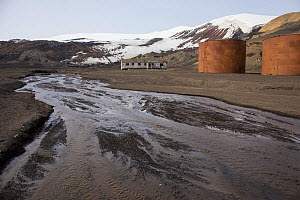 Meltwater stream with remains of fuel tanks from the whaling era 1911- 1931 and decaying building occupied by British Antarctic Survey scientists from the 1940s to 1970, Whaler's Bay, Deception Island... - Michel  Roggo