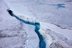 Aerial view of ice cap north-east of Sermeq Kujalleq Glacier with meltwater channel disappearing in a moulin, Sermersuaq / Greenland ice sheet, Greenland, Photographed for The Freshwater Project  -  Michel  Roggo