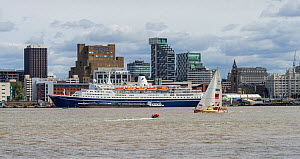 A yacht passing the Liverpool waterfront just after the start of the 2017 Clipper Round the World Race, with the Marco Polo cruise ship moored at the Pier Head landing stage. Merseyside, UK, August 20...  -  Alan  Williams