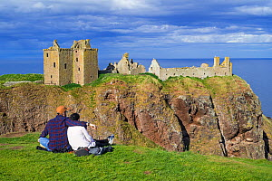 Tourists looking at Dunnottar Castle, ruined medieval fortress near Stonehaven on cliff along the North Sea coast, Aberdeenshire, Scotland, UK, May 2017  -  Philippe Clement