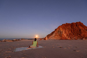 Moonrise over Cape Leveque with woman watching. Broome,  Dampier Peninsula, Kimberley, Western Australia. July 2016. Model released. - Jurgen Freund