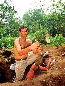 Cameraman Michael Pitts with newly hatched Komodo dragon (Varanus komodensis) at megapode mound where the female  laid her eggs. Komodo Island, Indonesia. 1995  -  Michael Pitts