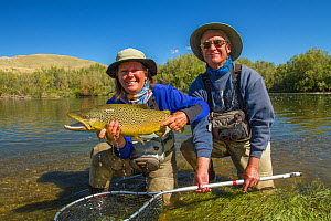 Man and woman  with prize 6lb male hook jawed Brown trout (Salmo trutta)  Beaverhead River, Montana, USA.  -  Phil Savoie