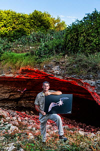 Director of Bat Conservation International's Bracken Cave Preserve standing at the mouth of Bracken Cave, holding one of his teaching placards, Bracken Cave, San Antonio, Texas, USA, July 2015.  -  Karine Aigner