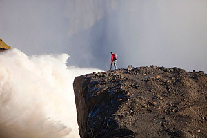 Man standing on cliff near water flowing out of the Karahnjukar dam and Halslon reservoir, a massive new controversial hydro electricity project in North East Iceland. It was created by damming the Jo... - Ashley Cooper