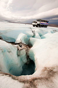 Twenty ton ice explorer truck  next to a Moulin, or sink hole for meltwater. Iceland, September 2010. - Ashley Cooper