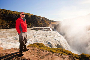 Man standing at the top of cliff near Godafoss waterfall, Akureyri, near northern Iceland  -  Ashley Cooper