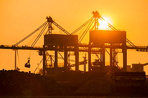 Cranes unloading coal  at sunset.  Tata steel works,  Ijmuiden, Netherlands, May 2013. - Ashley Cooper
