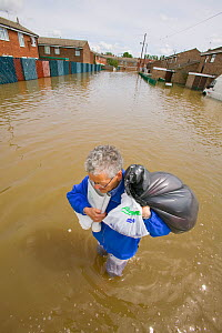 Resident carrying belongings through flood waters,  Toll Bar near Doncaster, South Yorkshire, England, UK, 28th July 2007.  -  Ashley Cooper