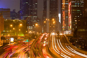 Office blocks lit up at night and cars in Hong Kong, China. February 2010. - Ashley Cooper