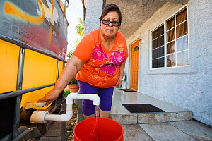 Woman filling a bucket from a tank outside her house supplied by a water charity. The charity supplies water to houses who have had no running water for over five months during the  2012-2017 Californ...  -  Ashley Cooper