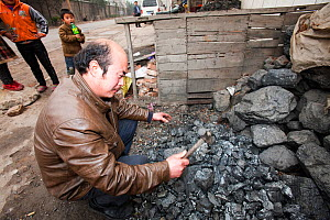 Man breaking up coal for domestic use. China, March 2009. In 2008 China officially became the worlds largest emitter of greenhouse gases. - Ashley Cooper