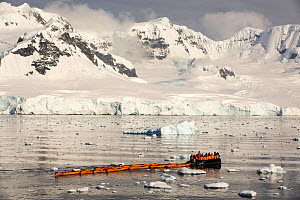 Members of an expedition cruise to Antarctica in a Zodiac with sea kayaks, Fournier Bay, Gerlache Strait, Antarctic Peninsula. - Ashley Cooper