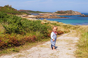 RF - Girl, aged 16 months, standing on path to Little Bay, St. Martin's, looking back, Isles of Scilly. August. Model-released. (This image may be licensed either as rights managed or royalty free.) - Merryn Thomas