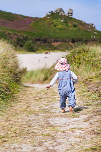 RF - Girl, aged 16 months, walking down path to Little Bay, St. Martin's, Isles of Scilly. August. Model-released. (This image may be licensed either as rights managed or royalty free.) - Merryn Thomas