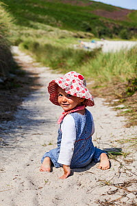 Girl, aged 16 months, sitting on path to Little Bay, St. Martin's, looking back, Isles of Scilly. August. Model-released.  -  Merryn Thomas