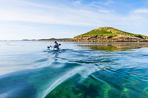 RF - Man on sit-ontop kayak, paddling around the uninhabited Eastern Isles, Isles of Scilly, August. Model-released. (This image may be licensed either as rights managed or royalty free.)  -  Merryn Thomas