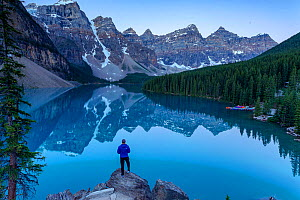 Person standing on rocks by looking over lake in the Rocky Mountains, with surrounding forest and kayaks stored, Alberta, Canada. July. - Felis Images